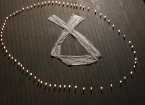 Un llaç blanca envoltat d'espelmes és el símbol utilitzat per recordar a les víctimes de la violència masclista. // Maria Roda