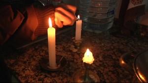 Una família utilitza espelmes en un tall de llum // Taula del Tercer Sector